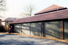 Real tiled roof and brick effect front posts on a block of Heritage garages.